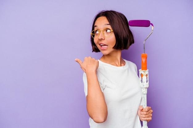 Mulher de raça mista jovem pintor segurando uma vara de tinta isolada na parede roxa aponta com o dedo polegar para longe, rindo e despreocupada.