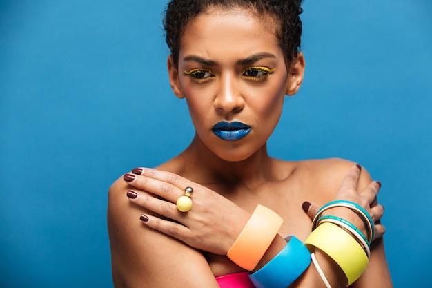 Mulher de raça mista tensa ou decepcionada colorida com maquiagem da moda e acessórios posando com as mãos cruzadas no peito, parede azul