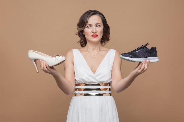 Mulher de raiva em um vestido branco segurando sapatos de salto alto e tênis e olhando com cara de ódio para o inferno. ela não quer assumir. foto de estúdio, interna, isolada em fundo marrom claro
