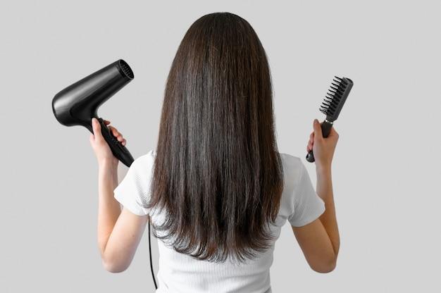 Mulher de retrato com escova e secador de cabelo