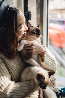 Mulher de retrato com gatos siameses