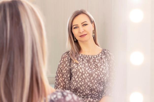Mulher de retrato com idade olha no espelho. reflexo no espelho. mulher idosa bonita