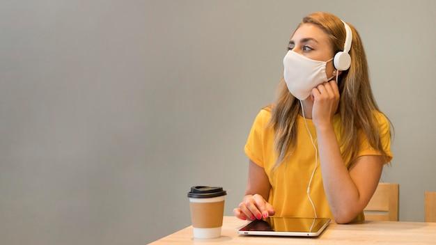 Mulher de retrato com máscara usando tablet