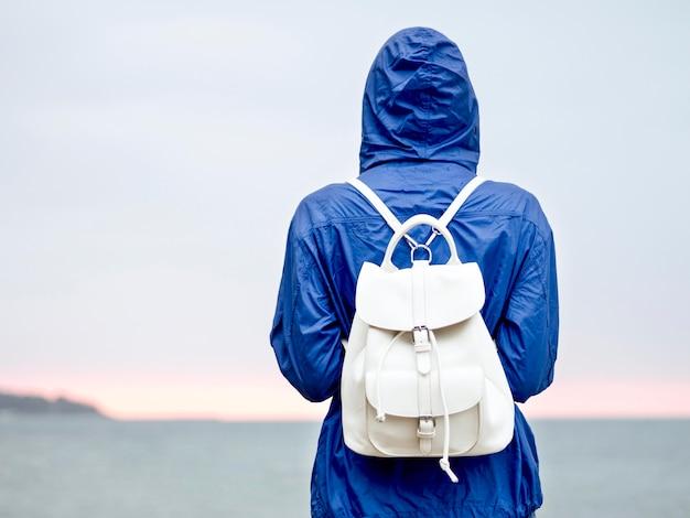 Mulher de retrato com mochila na costa do mar