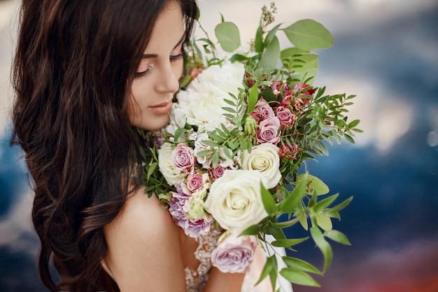 Mulher de retrato com olhos azuis e buquê de flores nas mãos na natureza