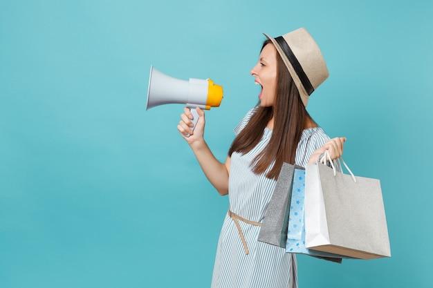 Mulher de retrato com vestido de verão, chapéu segurando sacolas de pacotes com compras depois das compras, grito no megafone, anuncia venda de descontos isolada em fundo azul pastel. copie o espaço para anúncio.