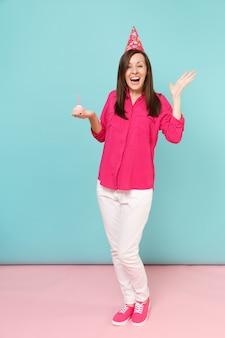 Mulher de retrato de corpo inteiro em blusa de camisa rosa, calça branca, chapéu de aniversário com cupcake posando isolado na parede pastel azul rosa brilhante.
