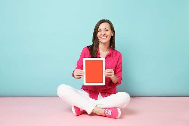 Mulher de retrato de corpo inteiro em blusa de camisa rosa, calça branca sentada no chão segura o tablet pc isolado na parede azul pastel de rosa brilhante.