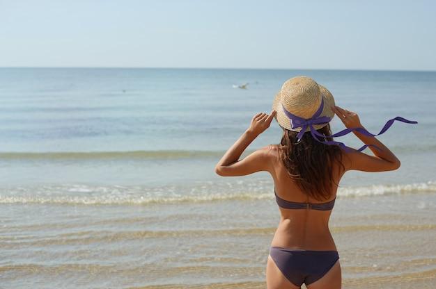 Mulher de retrato de verão em um chapéu olha para o mar