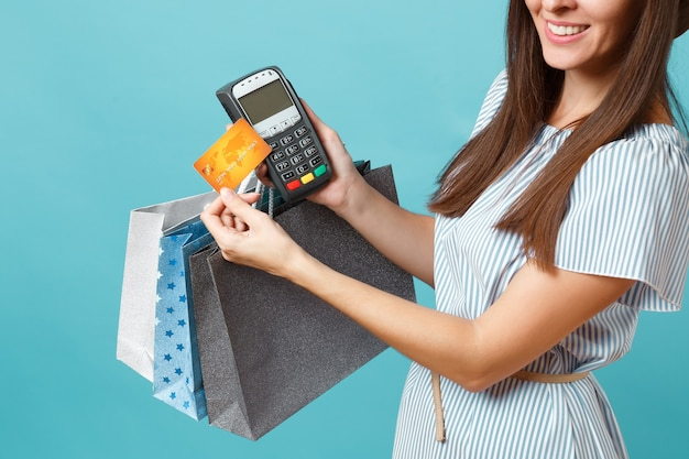 Mulher de retrato de vestido, chapéu segurando sacolas de pacotes com compras depois das compras, terminal de pagamento de banco moderno sem fio para processar e adquirir pagamentos com cartão de crédito isolados em fundo azul pastel.