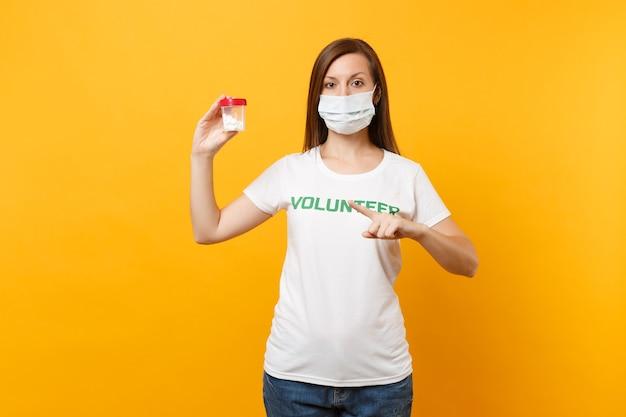 Mulher de retrato em t-shirt branca escrito voluntário do título verde de inscrição, máscara facial estéril com comprimidos de droga isolada no fundo amarelo. ajuda de assistência gratuita voluntária, conceito de saúde de graça de caridade