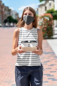 Mulher de retrato na rua com café usando máscara