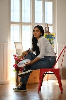 Mulher de retrato pintura sobre tela com pincel enquanto está sentado na cadeira moderna e confortável.