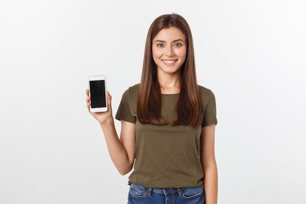 Mulher de riso que fala e que texting no telefone isolado em um branco.