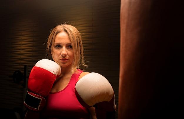 Mulher de rosa com luvas de boxe, treinamento com saco de pancadas.