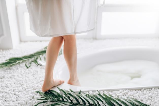 Mulher de roupão branco mergulha as pernas na banheira com espuma. interior luxuoso do banheiro com janela e decoração de ramo de palmeira
