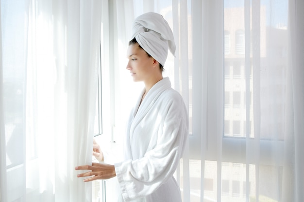 Mulher de roupão de banho ensolarado janela cortinas brancas