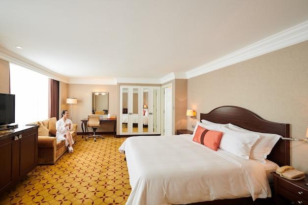 Mulher de roupão de banho sentada no sofá tomando café em um grande quarto de hotel com cama de casal