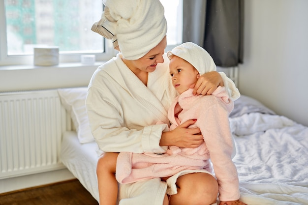 Mulher de roupão e toalha passa o tempo na cama com a filha menina