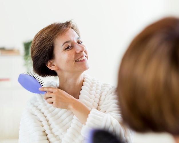 Mulher de roupão escovando o cabelo no espelho