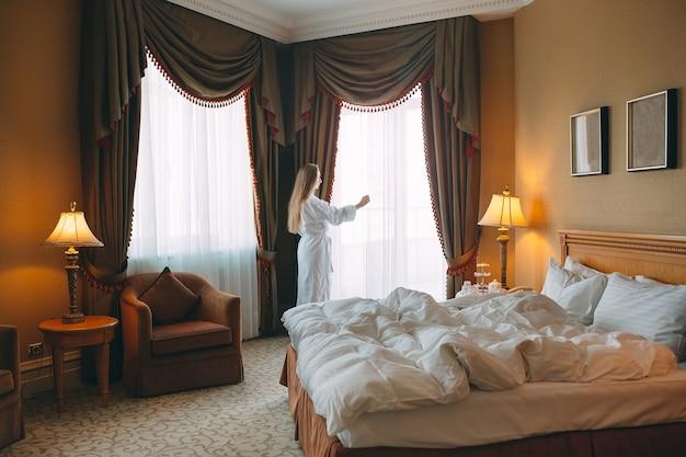 Mulher de roupão fica perto da janela no quarto de hotel.
