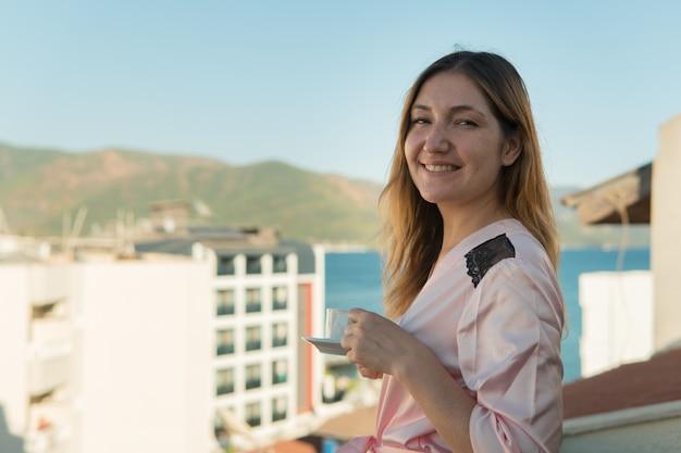 Mulher de roupão tomando café na varanda de seu quarto no hotel
