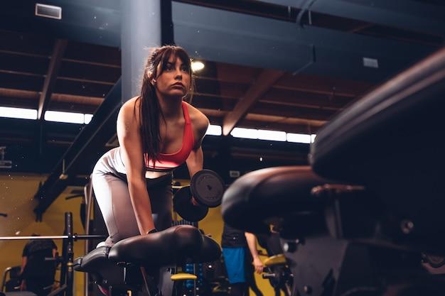 Mulher de roupas esportivas levantando peso na academia