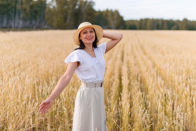 Mulher de saia e chapéu em um campo de trigo