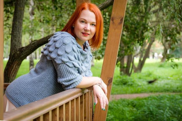 Mulher de saia e suéter de tricô em pé no terraço de madeira de sua casa de campo