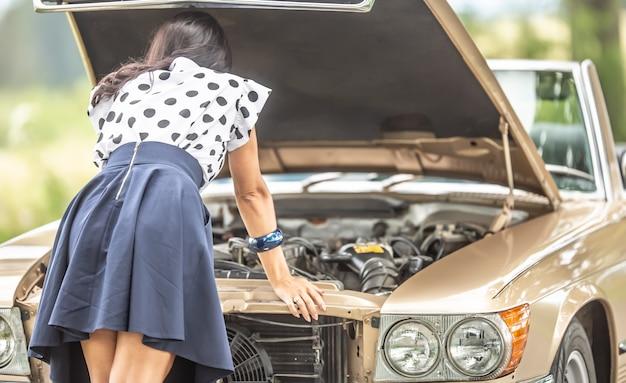 Mulher de saia se inclina para o capô aberto de um motor de carro conversível antigo após um colapso.