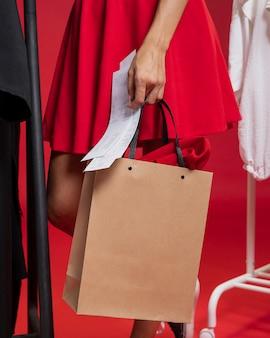 Mulher de saia vermelha à procura de roupas novas