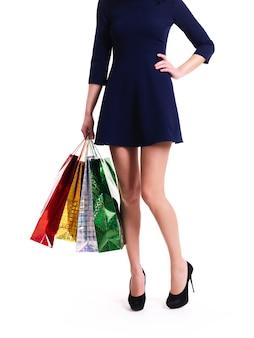 Mulher de salto alto com sacolas de compras em pé - isolado no branco.