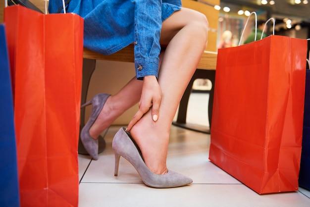 Mulher de sapatos de salto alto sentindo dores nos tornozelos