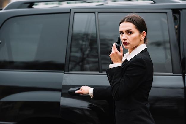 Mulher de segurança na frente do carro