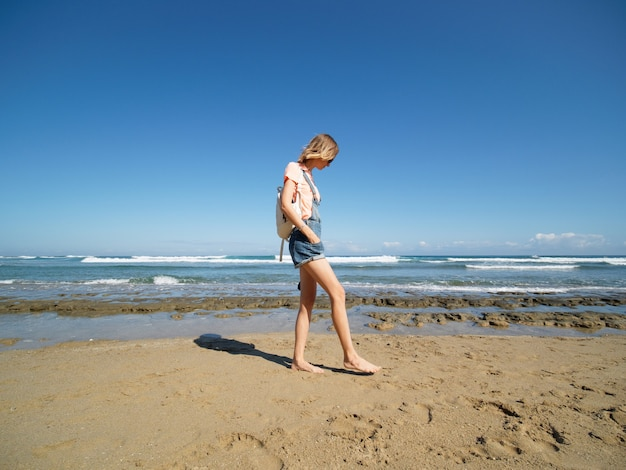 Mulher de shorts caminha na praia de areia. estilo de vida saudável. tiro de grande angular.