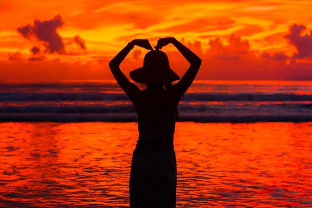 Mulher de silhueta com céu pôr do sol