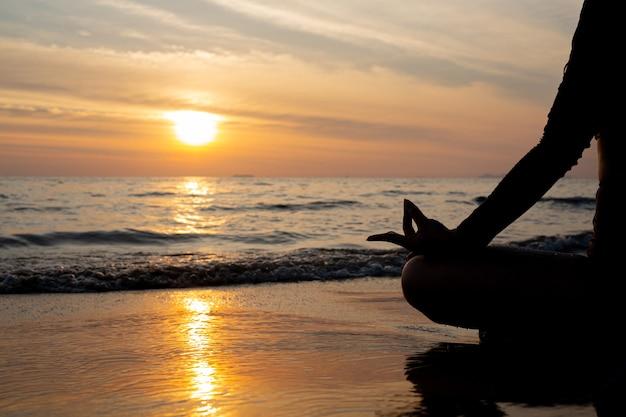 Mulher de silhueta praticando ioga na praia ao pôr do sol.