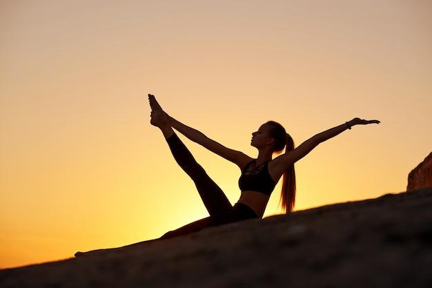 Mulher de silhueta praticando ioga ou alongamento ao pôr do sol ou nascer do sol