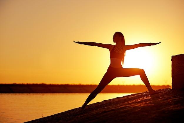Mulher de silhueta praticando ioga ou alongamento no cais da praia ao pôr do sol ou nascer do sol