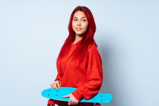Mulher de skatista adolescente isolada na parede branca com os braços cruzados e feliz
