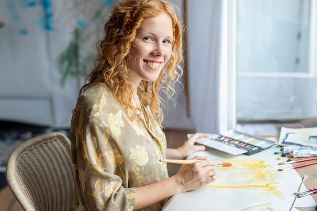 Mulher de smiley pintura dentro de casa