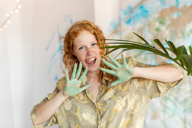 Mulher de smiley vista frontal com tinta nas palmas das mãos