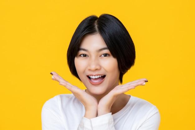 Mulher de sorriso agradável alegre colocando seu rosto feliz entre as mãos