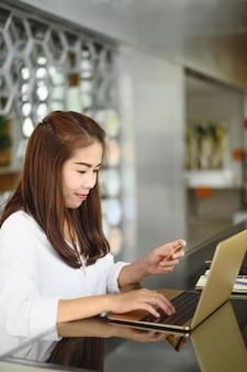 Mulher de sorriso asiática que guarda o telefone e que usa o laptop para fazer compras on-line.