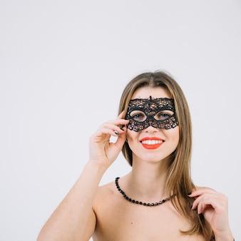 Mulher de sorriso atrativa na máscara do carnaval do disfarce no fundo branco