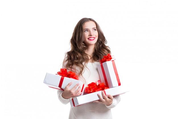 Mulher de sorriso atrativa prendendo caixas brancas com as fitas brancas com presentes.
