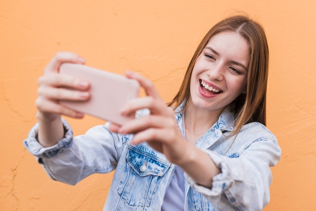 Mulher de sorriso atrativa que toma o selfie contra a parede bege