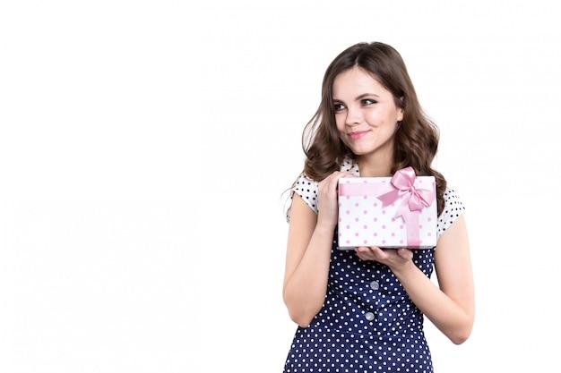 Mulher de sorriso bonita com a caixa de presente isolada no branco.