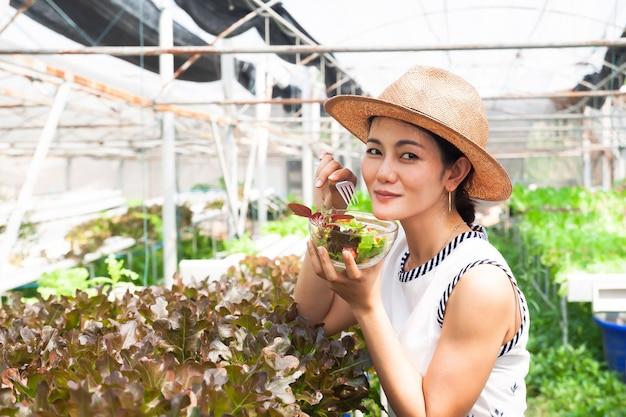 Mulher de sorriso bonita que come a salada fresca na exploração agrícola. conceito de estilo de vida saudável