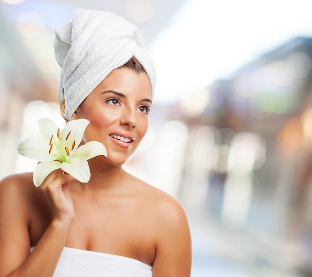 Mulher de sorriso com toalha e lírio